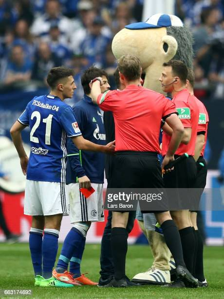 Coke of Schalke gives the red card back to referee Felix Zwayer during the Bundesliga match between FC Schalke 04 and Borussia Dortmund at...
