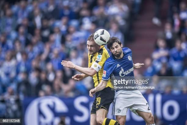 Coke of Schalke jumps for a header with Marcel Schmelzer of Dortmund during the Bundesliga match between FC Schalke 04 and Borussia Dortmund at...