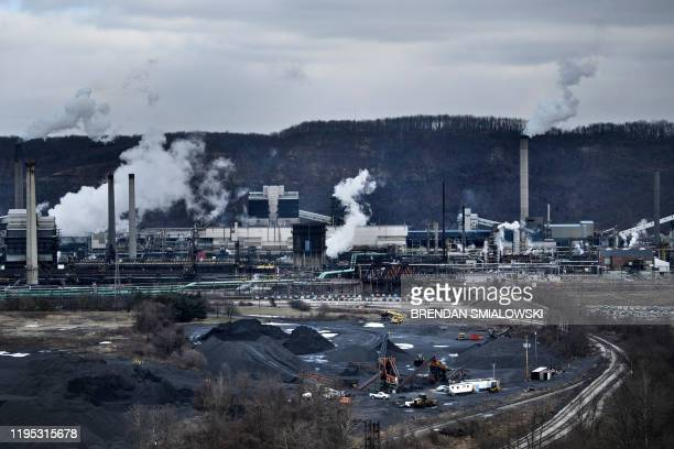 A coke storage area is seen as steam rises from the quench towers at the US Steel Clairton Works on January 21 in Clairton Pennsylvania White plumes...
