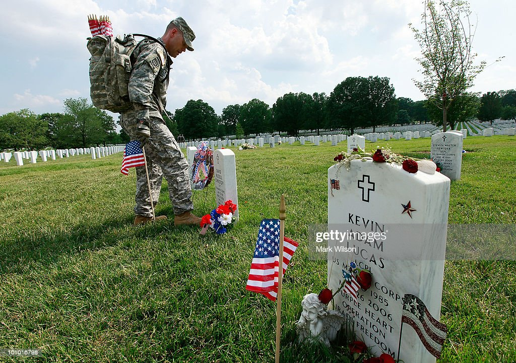 Col. Branden Robbins places a flag on gravesite at section 60, at Arlington National Cemetery May 27, 2010 in Arlington, Virginia. About 1,300 soldiers, sailors and Marines in about three hours placed a flag at each of the more than 300,000 gravestones at Arlington ahead of the Memorial Day weekend.