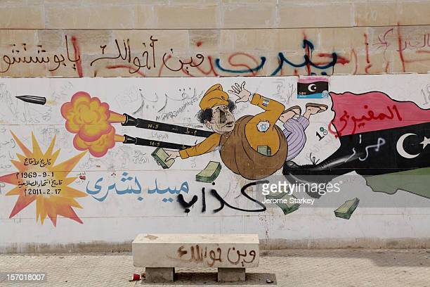Col Muammar Gaddafi sent tumbling by the boot of the Free Libyarebellion in street art daubed on the wall of Benghazi's customs house Teams of rebel...
