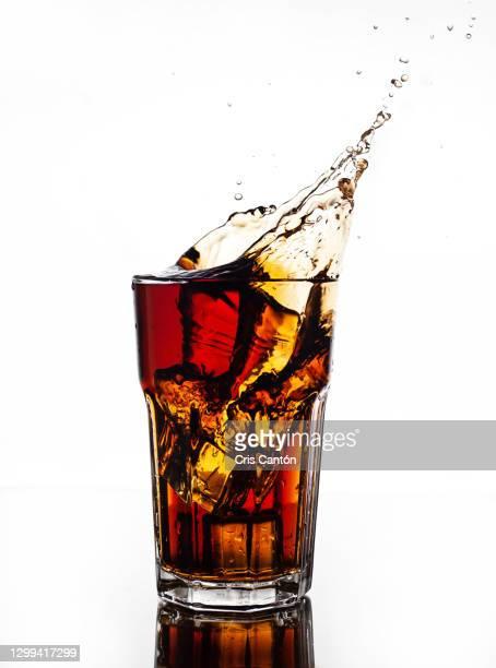 cola splash on tall glass - cris cantón photography fotografías e imágenes de stock