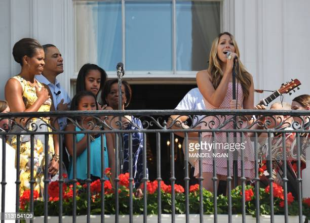 Colbie Caillat sings the National Anthem as First Lady Michelle Obama US President Barack Obama daughters Sasha and Malia and the First Lady's mother...