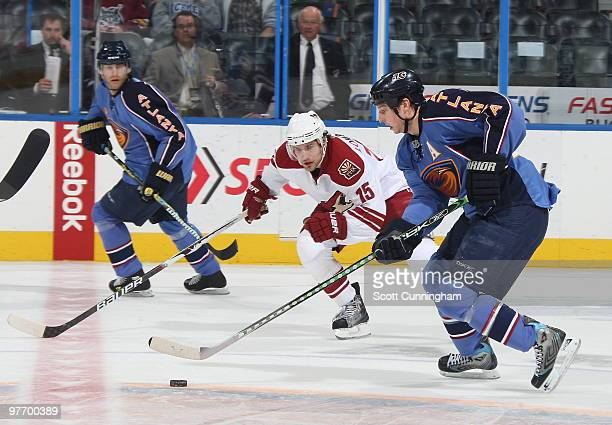 Colby Armstrong of the Atlanta Thrashers carries the puck against Matthew Lombardi of the Phoenix Coyotes at Philips Arena on March 14 2010 in...