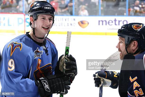 Colby Armstrong of the Atlanta Thrashers relaxes on the bench with Brad Larsen during the game against the Minnesota Wild at Philips Arena on March...