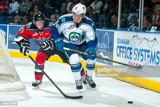 Colby Cave of Swift Current Broncos skates behind the net with the puck as Colten Martin of Kelowna Rockets back checks during second period on...
