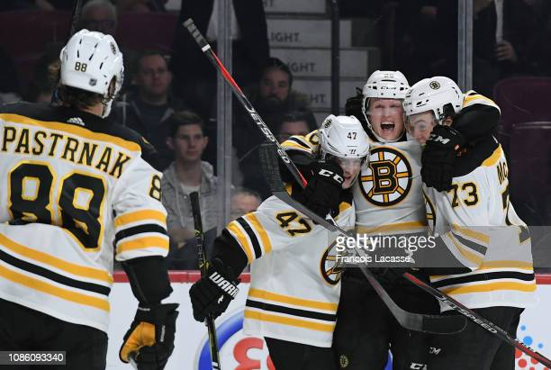 Colby Cave of the Boston Bruins celebrates with teammates after scoring a goal against The Montreal Canadiens in the NHL game at the Bell Centre on...