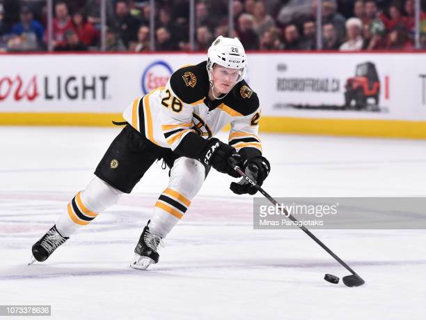 Colby Cave of the Boston Bruins reaches for the puck against the Montreal Canadiens during the NHL game at the Bell Centre on November 24, 2018 in...