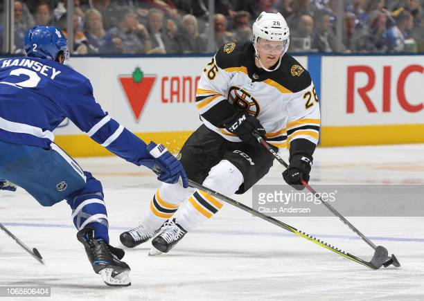 Colby Cave of the Boston Bruins skates with the puck against Ron Hainsey of the Toronto Maple Leafs during an NHL game at Scotiabank Arena on...