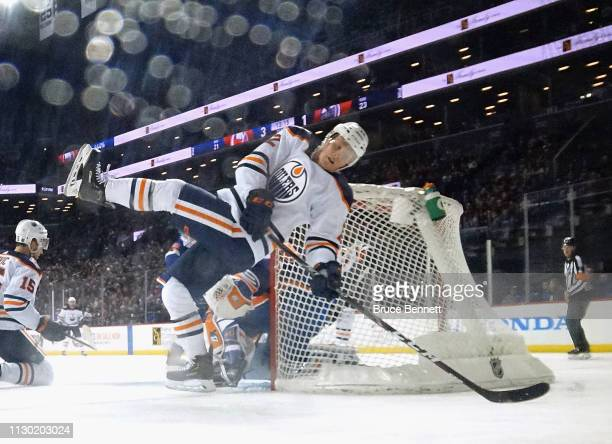 Colby Cave of the Edmonton Oilers is tripped up against the New York Islanders at the Barclays Center on February 16, 2019 in the Brooklyn borough of...