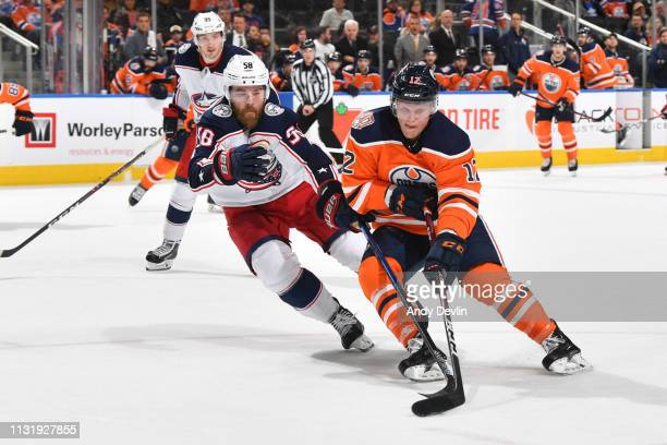Colby Cave of the Edmonton Oilers skates with the puck while being pursued by David Savard of the Columbus Blue Jackets on March 21, 2019 at Rogers...
