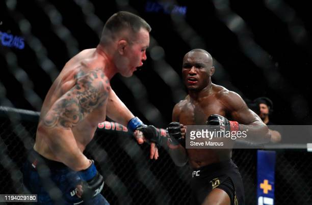Colby Covington falls back from a punch by UFC welterweight champion Kamaru Usman in the fifth round of their welterweight title fight during UFC 245...