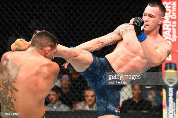 Colby Covington kicks the head of Rafael Dos Anjos of Brazil in their interim welterweight title fight during the UFC 225 event at the United Center...