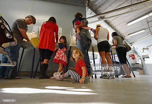 Colby Klein seated on the floor waits for her parents Jenine Kanell and George Klein holding her twin sister Audrey Klein to cast their ballots as...