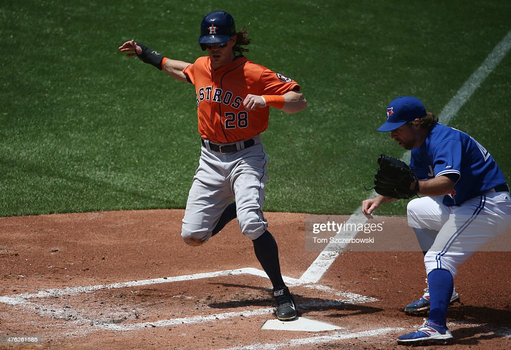Colby Rasmus #28 of the Houston Astros scores a run on a wild pitch in the second inning during MLB game action as R.A. Dickey #43 of the Toronto Blue Jays attempts a late tag on June 7, 2015 at Rogers Centre in Toronto, Ontario, Canada.