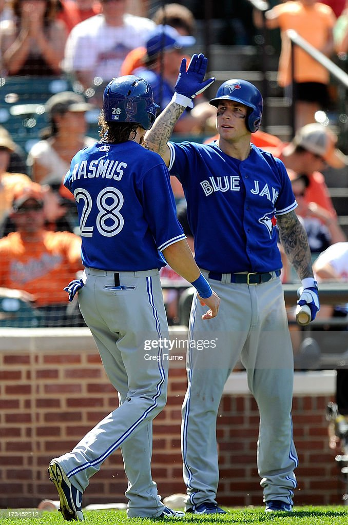Colby Rasmus #28 of the Toronto Blue Jays celebrates with Brett Lawrie#13 after scoring in the ninth inning against the Baltimore Orioles at Oriole Park at Camden Yards on July 14, 2013 in Baltimore, Maryland.