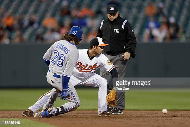 Colby Rasmus of the Toronto Blue Jays slides safely into second base for a double as shortstop JJ Hardy of the Baltimore Orioles waits for the throw...