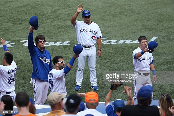 Colby Rasmus of Toronto Blue Jays and Jose Bautista and third base coach Luis Rivera and Steve Tolleson salute the fans in the fourth inning during...