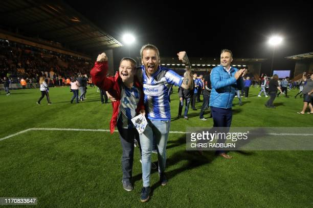 Colchester United fans invade the pitch after their team won the penalty shoot out during the English League Cup third round football match between...