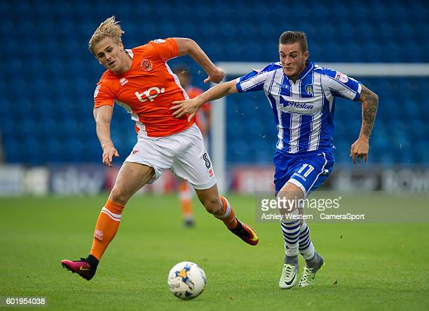 Colchester United's Ben Dickenson holds off the challenge from Blackpool's Brad Potts during the Sky Bet League Two match between Colchester United...