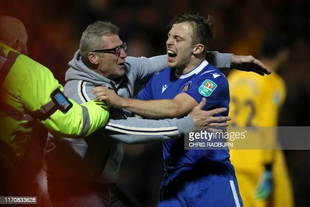 Colchester United's English midfielder Tom Lapslie celebrates with a pitch invader after scoring his winning goal in the penalty shoot out during the...
