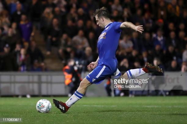 Colchester United's English midfielder Tom Lapslie scores his goal in the penalty shoot out during the English League Cup third round football match...