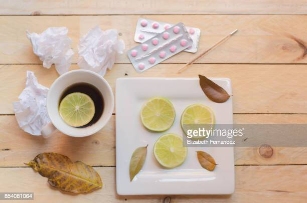 Cold and flu concept. Cup of tea, lemon slices, thermometer, tissues and pills.