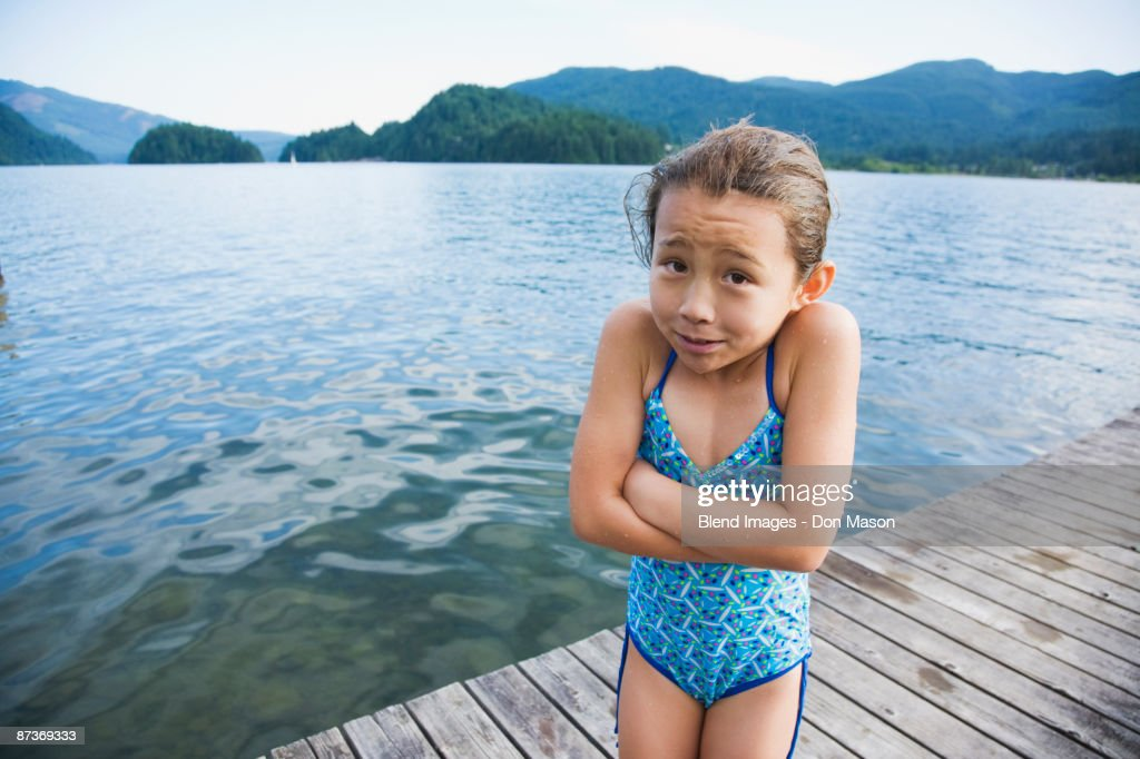 Cold Asian girl standing on dock : Stock Photo