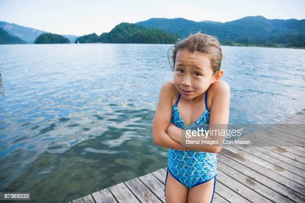Cold Asian girl standing on dock