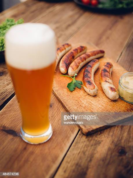 Cold beer with grilled bratwurst sausages on a wooden table