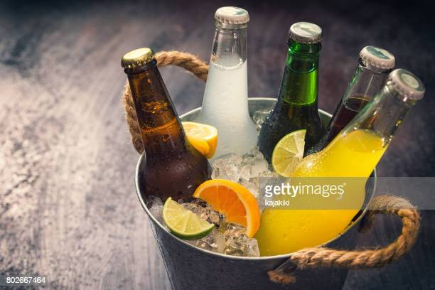 cold bottles of various drinks in the ice bucket - cold drink stock pictures, royalty-free photos & images