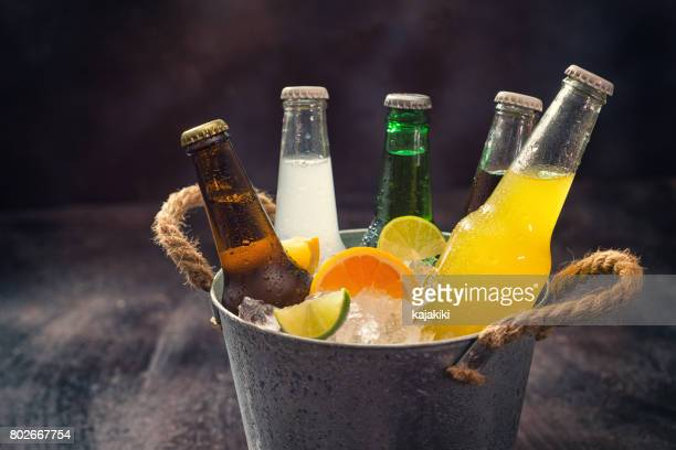 cold bottles of various drinks in the ice bucket - bibita foto e immagini stock