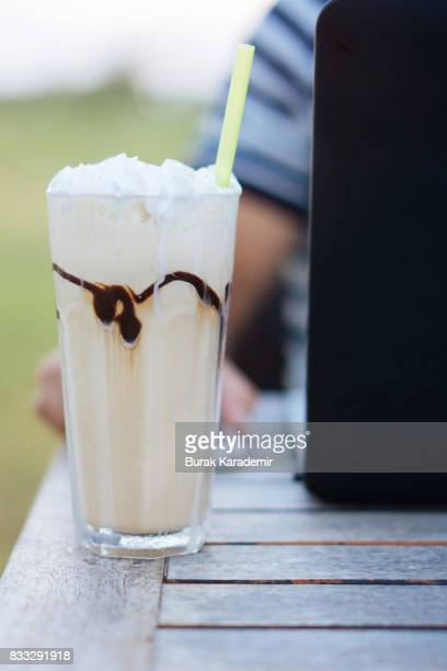 Cold chocolate with whipped cream topping in glass on summer