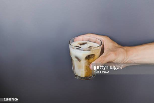 cold coffee drink in the hands on a gray background - coffee drink stock pictures, royalty-free photos & images