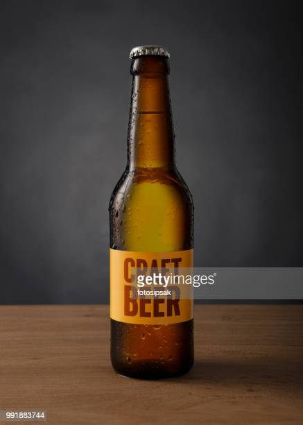 cold craft beer bottle with custom made label on the table against black background