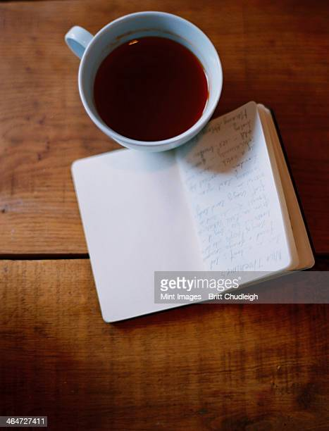 A cold cup of coffee and a handwritten journal.