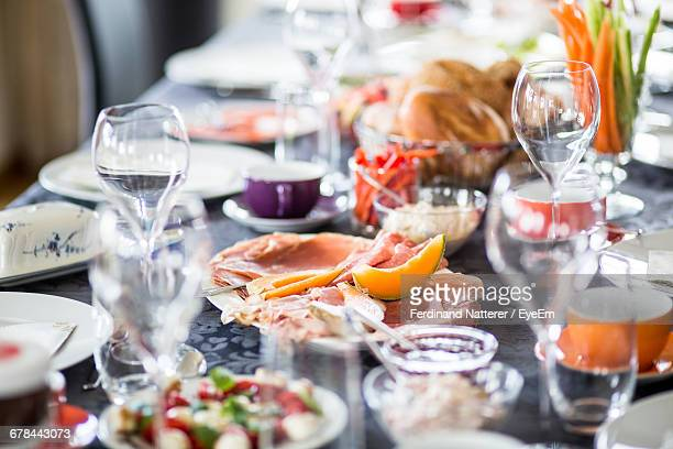 Cold Cuts And Fruits With Vegetables Amidst Plates On Table