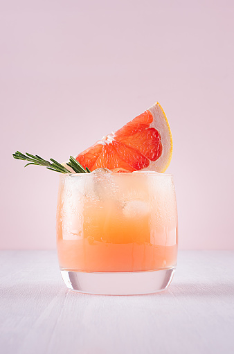 Cold detox cocktail of grapefruit juice with ice, rosemary, slices citrus on soft light pink and white background. 975705080