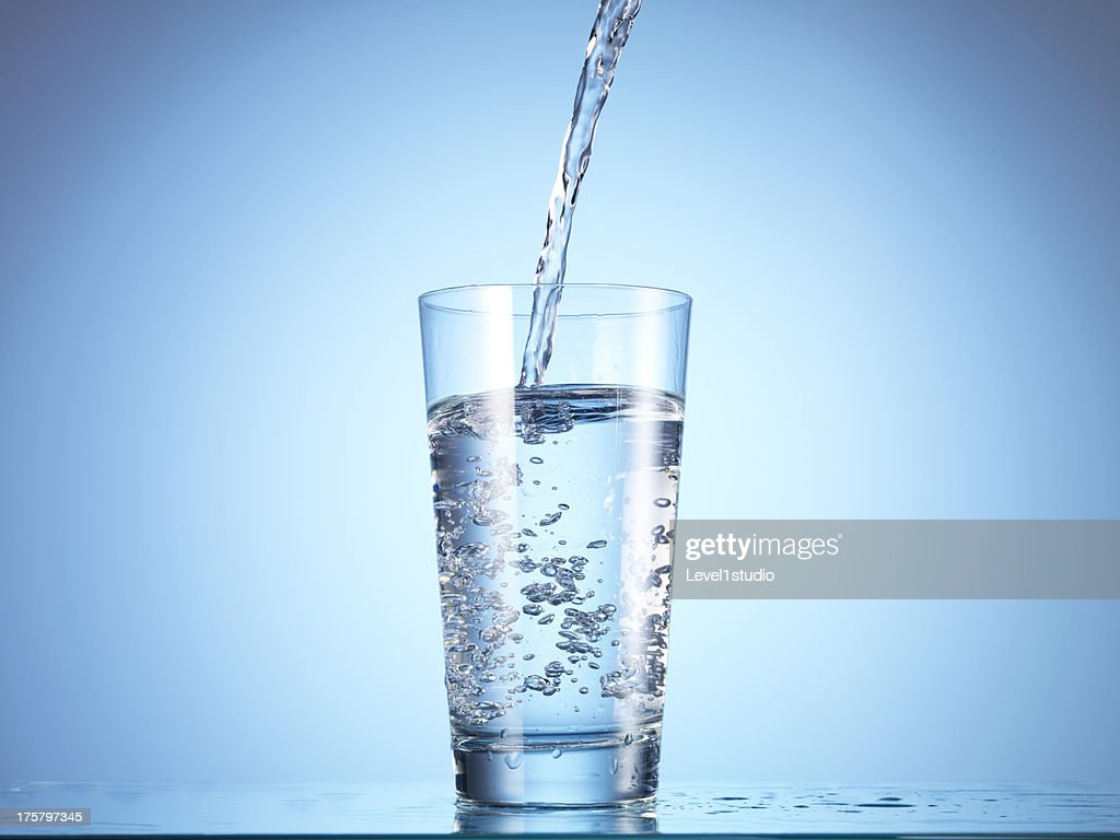 Cold drink water being poured into glass : Stock Photo