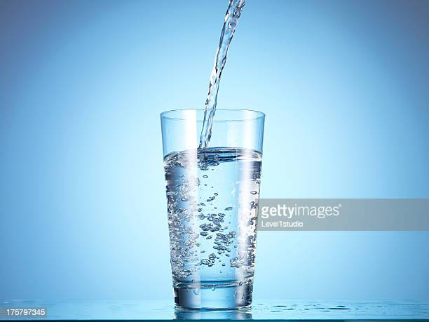cold drink water being poured into glass - drinking glass stock pictures, royalty-free photos & images