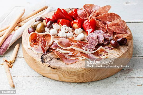 Cold meat plate and grissini bread sticks on wooden background