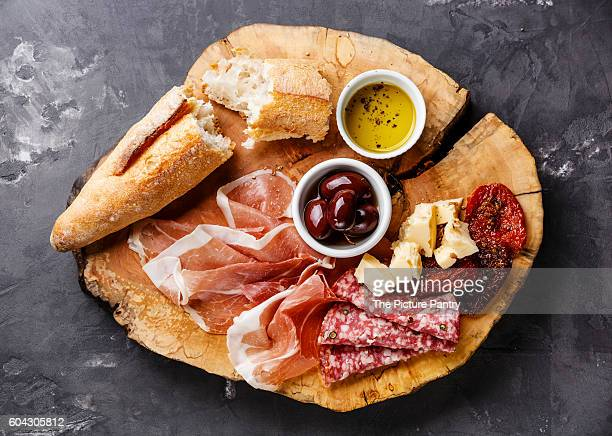 Cold meat plate with prosciutto, salami, bread and olives on wooden board on gray concrete stone background