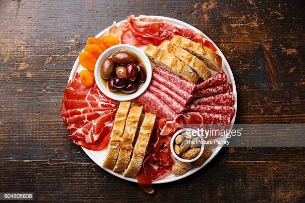 Cold meat plate with prosciutto, salami, ciabatta bread and olives on wooden background
