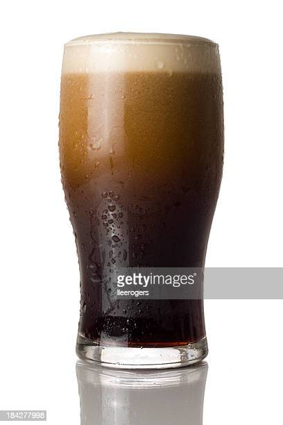 Cold pint of stout settling isolated on a white background