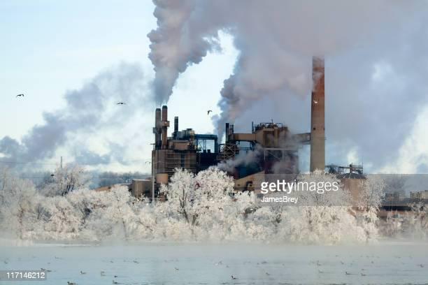 Cold Reality; Factory Smoke Stacks Amid Winter Wonderland Environment