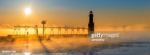 Cold steaming Lake Michigan at Sunrise with iconic Lighthouse