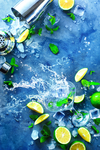 Cold summer drink splash with mint leaves, lime slices, and ice cubes. Mojito cocktail ingredients with copy Sunlight and refreshment concept. - gettyimageskorea