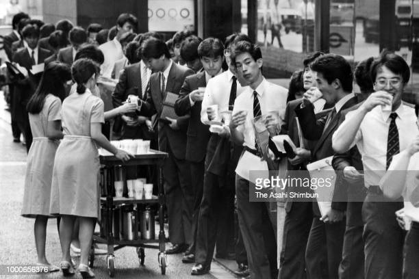 Cold tea are distributed to students queueing for meetings at Sanwa Bank headquarters on August 20 1986 in Tokyo Japan