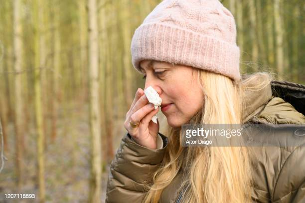 cold woman in winter in the woods holding with her hand a tissue on her nose - mucus stock pictures, royalty-free photos & images