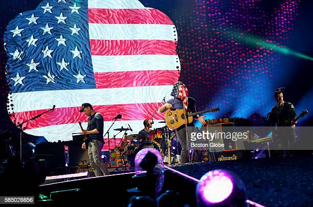 Coldplay frontman Chris Martin briefly drapes an American flag over his face and the microphone during a performance at Gillette Stadium in...